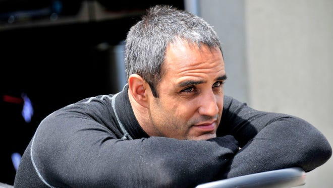 Juan Pablo Montoya relaxes in the garage are after a practice session at the Indianapolis Motor Speedway on May 19, 2014.