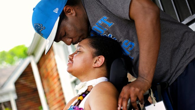 Curtis White, 45, kisses his daughter forehead Dreia Davis, 19, at front porch of their home in Detroit on Wednesday, June 17, 2015. Dreia Davis in 2009, was shot in the head during a drive-by shooting. Since the shooting, she's had multiple surgeries, was on life support and now paralyzed on the left side of her body.