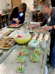 """Workers prep baked goods for the """"Cookie Walk"""" at St."""