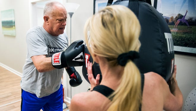 Ira Paulk his a punching bag as his coach Jennifer Mathews holds it steady during a boxing class for people with Parkinson's disease at Core Balance on Wednesday, May 10, 2017.