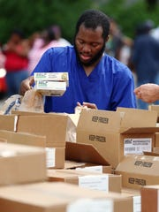 """Brian Jones, Indianapolis, picks out groceries from the CARE Mobile Food Pantry on Monday, June 15, 2015, at Nazarene Missionary Baptist Church on East 38th Street. """"I'm just living from one check to another, and I find it hard to spend time with my family,"""" Jones said. """"This means a lot. It really gives back to the community."""""""