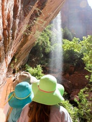 A family looks over the scenery at the Emerald Pools lookout at Zion National Park, Utah.