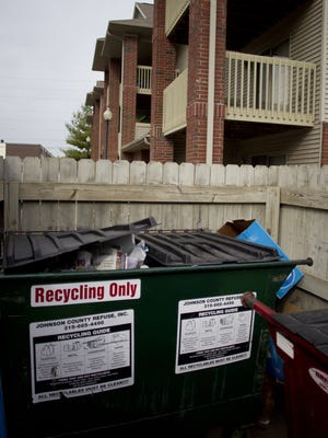 Recycling and trash bins are seen on Oct. 20, 2013, at the Benton Villa residential complex in Iowa City. Benton Villa was among the apartment buildings that took part in a recycling pilot program.
