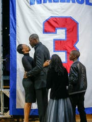 Pistons great Ben Wallace and his wife, Chanda, and children, Bryce and Bailey, stand up in front of his No. 3 that will be retired to the rafters during halftime at the Palace Saturday.