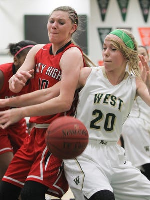 City High's Ashley Joens, left, and Maddie Huinker fight for a rebound during their Jan. 8 game at West High. Both City and West are gearing up for postseason action.