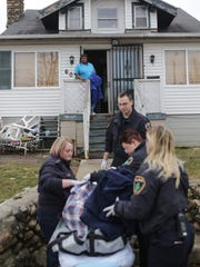 Lisa Gaines of Flint watches from her porch as paramedics