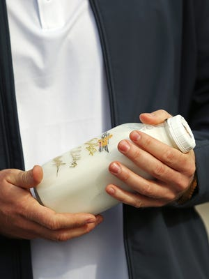 Indianapolis Colts' Matt Overton holds a commemorative bottle of milk before raising the flags above the Wing and Wheel logo at Indianapolis Motor Speedway, March 22, 2016.
