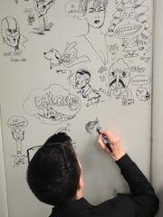 Alison Bechdel autographs a wall at Daydreams Comics