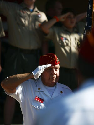 Jim Brandreth of the Marine Corps League presents the American flag and solutes during the Memorial Day service at Riverside Park in Bonita Springs on Monday, May 30, 2016. (Dorothy Edwards/Staff)