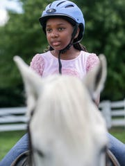 Kennedy Carter, 11, of Detroit rides the pony Magic with help from volunteers during the Detroit Horse Power day camp at Ringside Equestrian center in New Hudson, Mich. on Tuesday, July 26, 2016.