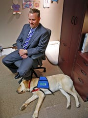 """Ryan Bland, supervising deputy prosecutor in the Johnson County child abuse and sex crimes division, sits next to the napping Johnson County """"courthouse dog,"""" Nanook."""