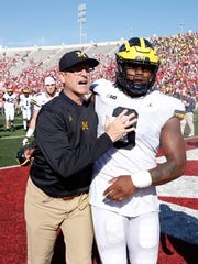 Jim Harbaugh celebrates with Rashan Gary after the 27-20 victory in overtime over Indiana, Oct. 14, 2017 in Bloomington, Ind.