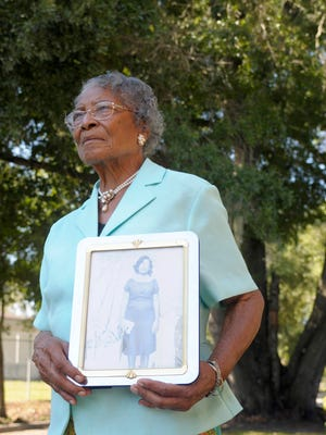 Recy Taylor, 90, holds a photo of herself from her days in Abbeville, Ala., outside her home in Winter Haven, Fla., in this photo taken Thursday, Oct. 7, 2010.  Taylor was brutal sexual assault by seven white men in 1944. The perpetrators were never brought to justice. In 2011, the state of Alabama issued a formal apology to Taylor.