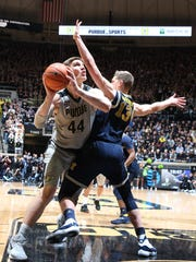 Purdue center Isaac Haas takes a shot against Michigan forward Moritz Wagner during the first half Thursday.