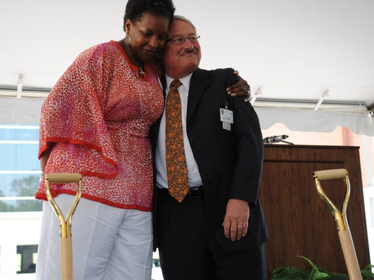 Daedra Charles-Furlow (cq) gives a hug to Dr. John Bell, Director of the Cancer Institute after a groundbreaking ceremony for the new UT Medical Center Cancer Institute on Thursday, July 14, 2011. The $25 million building will be 100,000 square feet and should be completed in about a year. Charles-Furlow, a cancer survivor, is a former lady Vol basketball player, coach and currently serves as the Director of Character Development for the Lady Vols basketball team.