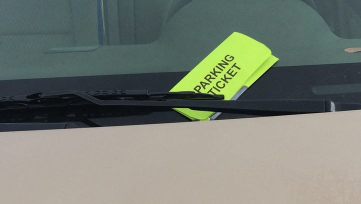 A car with a parking ticket is parked on a city street.