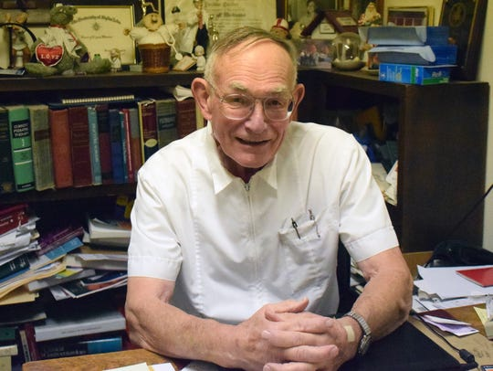 Dr. H. Lynn Moore, 84, poses for a photo in his office