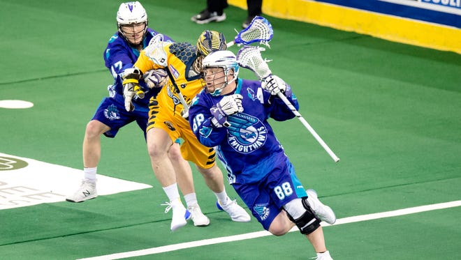 Cody Jamieson of the Rochester Knighthawks scrambles away from the defense of the Georgia Storm.