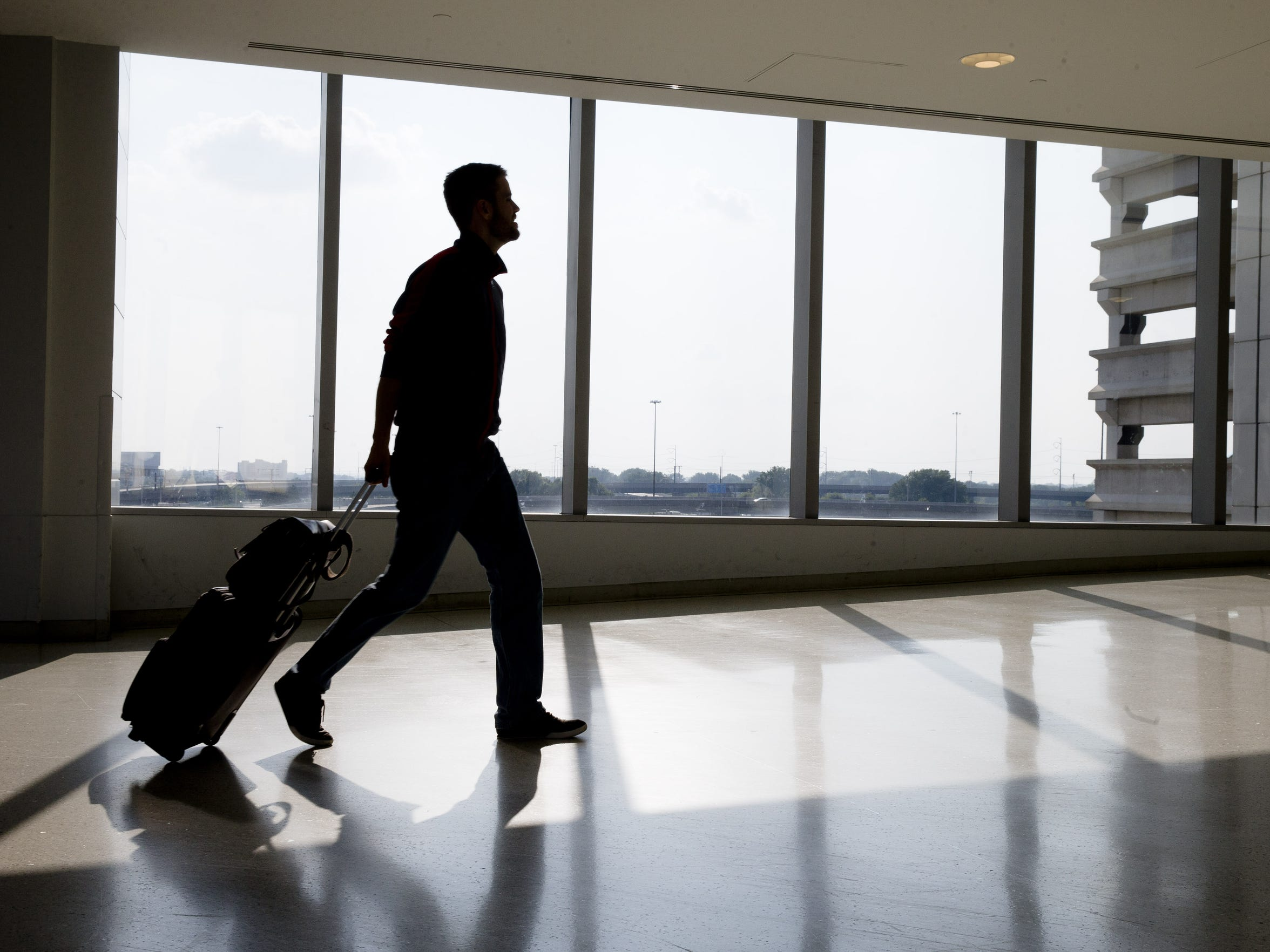 A traveler passes through Philadelphia International Airport on July 31, 2014. Officials are considering a plan that would expand rail service to the airport.