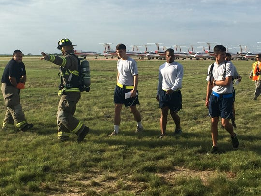 Firefighter Shane Mathews leads volunteer 'victims' to awaiting buses that will take them to local hospitals, where training will continue Thursday, July 13, 2017, at San Angelo Regional Airport.