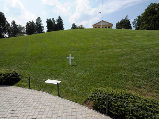 Robert F. Kennedy's grave is marked by a simple cross and stone at Arlington National Cemetery.