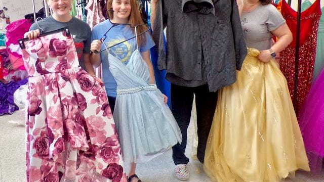 The Boone High School student council operates Cinderella's Closet, a free resource for students who may not be able to afford dresses and other formal wear for school dances. Left to right: Sierra Sherry, Mackenzie Peterson, Benjamin Lumley and teacher Shannon Lumley. Photo by Sara Jordan-Heintz