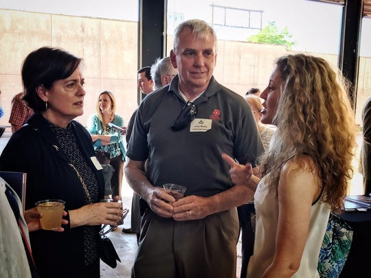 Liz and Larry Martin visit with Leslie Harrelson, right, at the Give Light Awards. Martin is general manager of United Supermarkets.