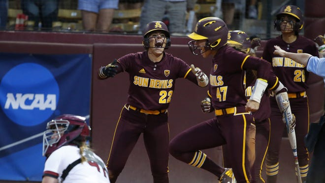 Arizona State's Kindra Hackbarth (22) and teammate Morgan Howe (47) celebrate scoring during the 5th inning of game 2 of the NCAA super regional at ASU Farrington Stadium in Tempe on May 26, 2018.