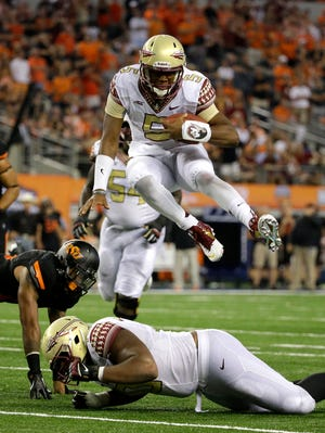 Florida State quarterback Jameis Winston (5) leaps over guard Josue Matias as Oklahoma State safety Jordan Sterns, left, is unable to stop Winston from reaching the end zone for a touchdown in the second half of an NCAA college football game, Saturday, Aug. 30, 2014, in Arlington, Texas.