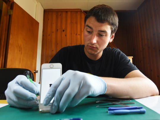 Kevin Idleman repairs an iPhone screen at Screenshot Repair on Maple Avenue in Zanesville.