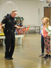 Officer Paul Webb jumps rope with a few girls Thursday