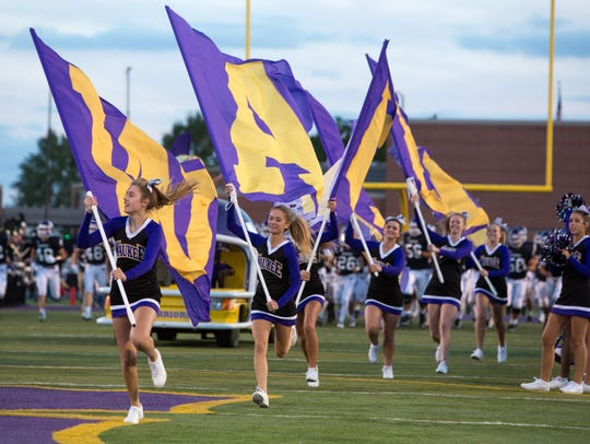 Waukee High School cheerleaders lead the team out on