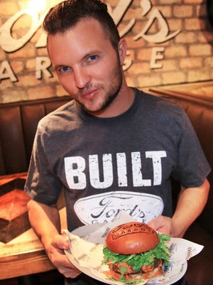"""MasterChef"" runner-up and Fort Myers native Derrick Peltz shows off the limited-edition California Rocker Burger he created for Ford's Garage. Proceeds benefit Susan G. Komen Southwest Florida."