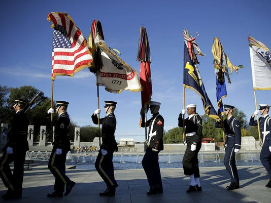 Image: The U.S. military honor guard removes the colors at the National World War II Memorial on Veteran's Day in Washington