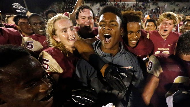 Riverdale's injured quarterback and Homecoming King Christian Souffront celebrates the team's final play victory 30-28 with his team following the game, on Friday, Sept. 29, 2017, at Riverdale.