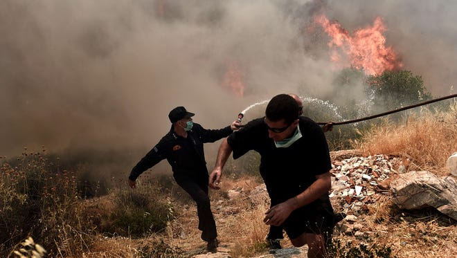 People and firefighters flee from a fire progressing in Athens. Greece appealed for EU help to battle wildfires raging on the outskirts of Athens and in the southern Peloponnese region that forced the evacuation of several villages.