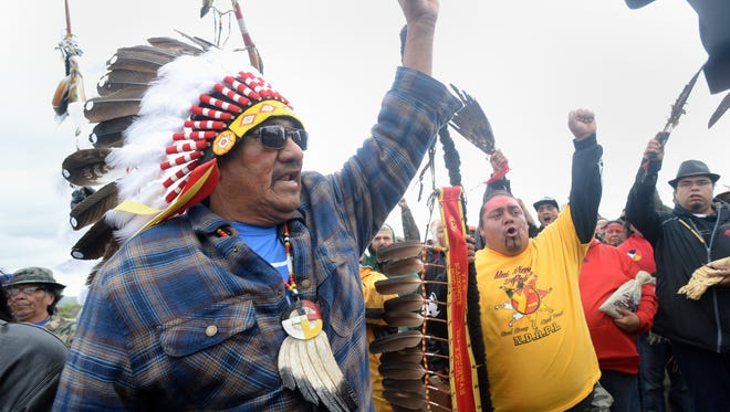 JR American Horse, left, raises his fist with others while leading a march to the Dakota Access Pipeline site in southern Morton County North Dakota.