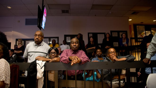 Current East Stuart resident Albert Brinkley (left) and former Stuart resident Anselme Marcelin and his wife, Alerte Marcelin (left), stand outside the packed chambers during the city of Stuart Commission meeting Wednesday, Feb. 1, 2017, where public comments regarding Commissioner Eula Clarke were heard.