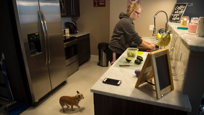 Mieka Wagner prepares guacamole with the help of her dog, Peanut, in her new McCurdy apartment Friday evening. Wagner moved in to her one-bedroom apartment Sunday.