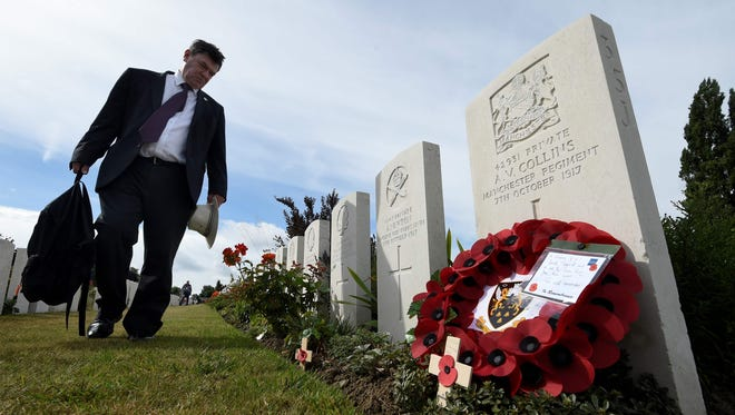 A visitor walks past headstones of soldiers who fell in World War I at The Tyne Cot Commonwealth War Graves Cemetery in Zonnebeke on July 31, 2017.