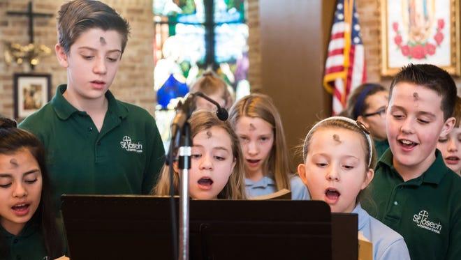 St. Joseph School students sing hymns during Mass on Ash Wednesday at St. Joseph Catholic Church.