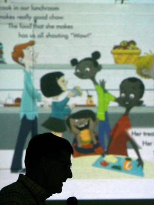 Author Paul Orshoski reads one of his books, while it is projected on the wall of the gymnasium, to students at Prospect Elementary School Monday morning.