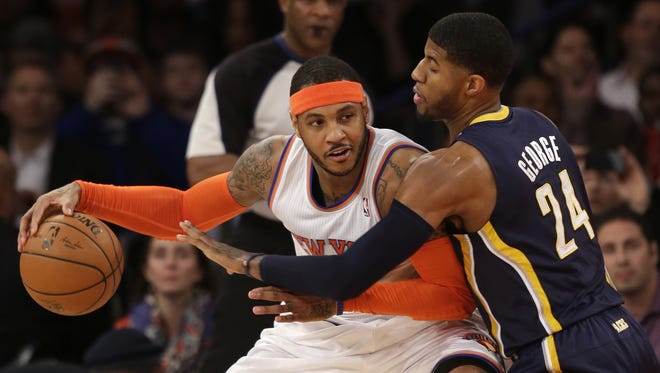 FILE - In this March 19, 2014, file photo, New York Knicks' Carmelo Anthony, left, tries to move around Indiana Pacers' Paul George during the first half of an NBA basketball game at Madison Square Garden in New York. Two people with knowledge of the details say that Anthony has informed the Knicks he intends to become a free agent.