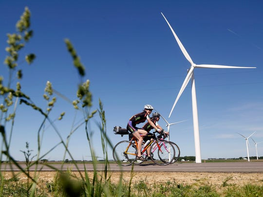 Cyclists make their way past the windmills Sunday, June 4, 2017, during the first day of the RAGBRAI pre-ride route inspection in northwestern Iowa. Each year, organizers and a select group of invited cyclists ride the route and inspect the towns before to make sure they are ready for thousands of cyclists that will be coming through for the The Register's Annual Great Bike Ride Across Iowa the next month.