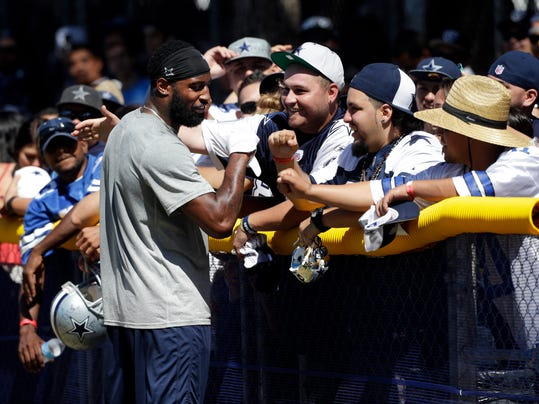 Dallas Cowboys safety Ahmad Dixon greets fans before the team's joint football practice with the Oakland Raiders on Tuesday, Aug. 12, 2014, in Oxnard, Calif. (AP Photo/Jae C. Hong)