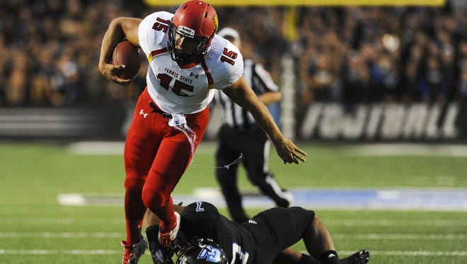 In this Sept. 19, 2015, photo, Ferris State quarterback Jason Vander Laan (15) is tackled by Grand Valley linebacker David Talley (7) during an NCAA college football game at Lubbers Stadium in Allendale, Mich.