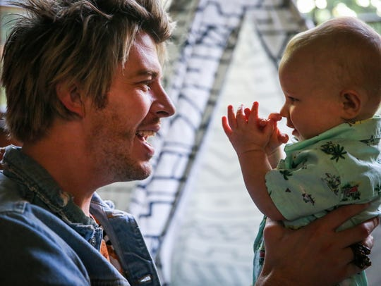 Taylor Harris plays with his 10-month-old son Bly on