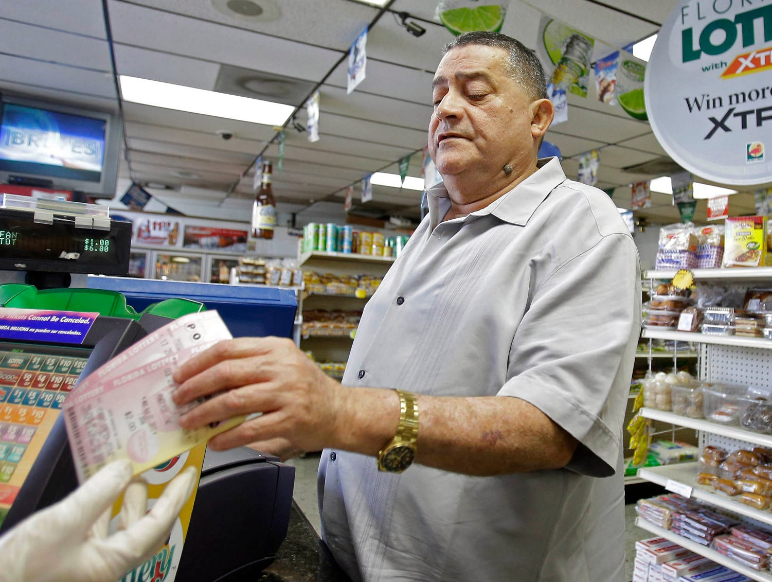 Remberto Gonzalez purchases Powerball tickets at a store in Hialeah, Fla.