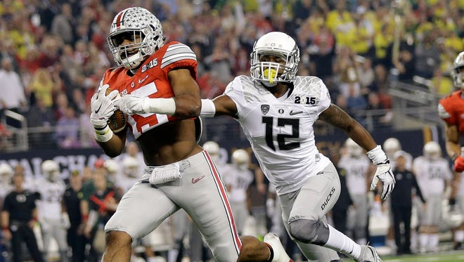 Ohio State's Ezekiel Elliott runs past Oregon's Chris Seisay for a touchdown during the first half of the NCAA college football playoff championship game Monday, Jan. 12, 2015, in Arlington, Texas. (AP Photo/Eric Gay)
