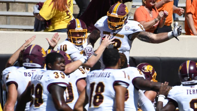 Central Michigan quarterback Cooper Rush (10) and tight end Tyler Conklin (83) celebrate after beating Oklahoma State at Boone Pickens Stadium in Stillwater, Oklahoma.